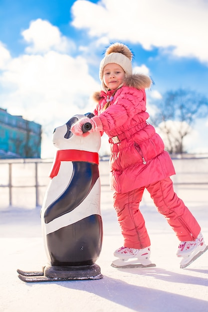Little happy girl skating on the ice-rink Premium Photo