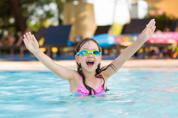 Little happy girl swimming in the outdoor pool with diving glasses on a sunny summer day Premium Photo