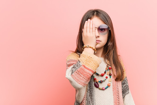 Little hippie girl having fun covering half of face with palm. Premium Photo