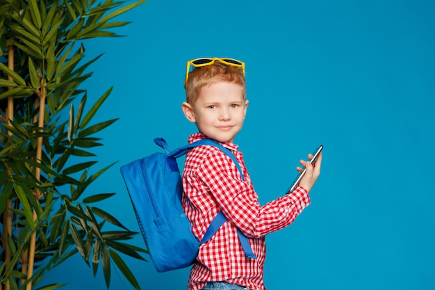 Little hipster boy with backpack and sunglasses holding telephone Premium Photo