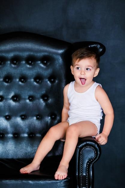 赤いハートの風船と肘掛け椅子に座っている白いtシャツで2歳の小さな幼児男の子 Premium写真