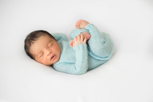 Маленький младенец лежит на маленьком белом стуле в синих вязаных пижамах Бесплатные Фотографии