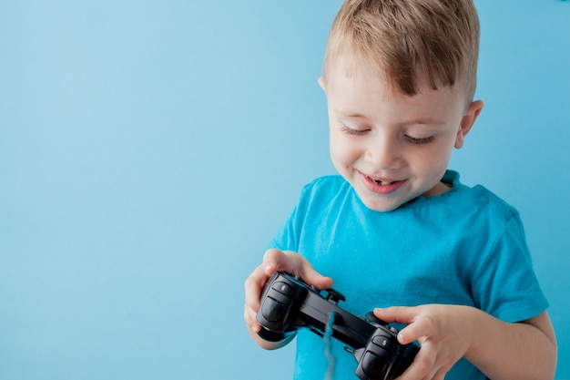 Little kid boy 2-3 years old wearing blue clothes hold in hand joystick for gameson blue background children studio portrait. people childhood lifestyle concept. mock up copy space Premium Photo