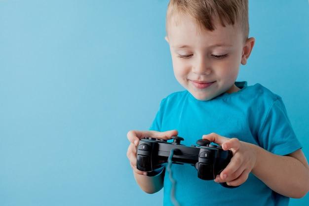 青い服を着ている2〜3歳の小さな男の子は、ゲームソンの青い背景の子供たちのスタジオの肖像画のジョイスティックを手に持っています。 Premium写真
