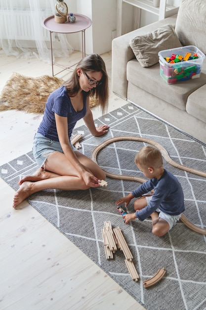Little kid boy and his mother playing with railway sitting on the floor Premium Photo