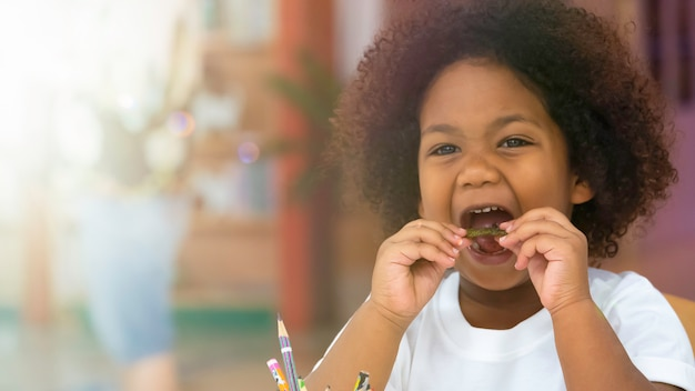 Little kid children smiling enjoy eating snack with happiness. Premium Photo