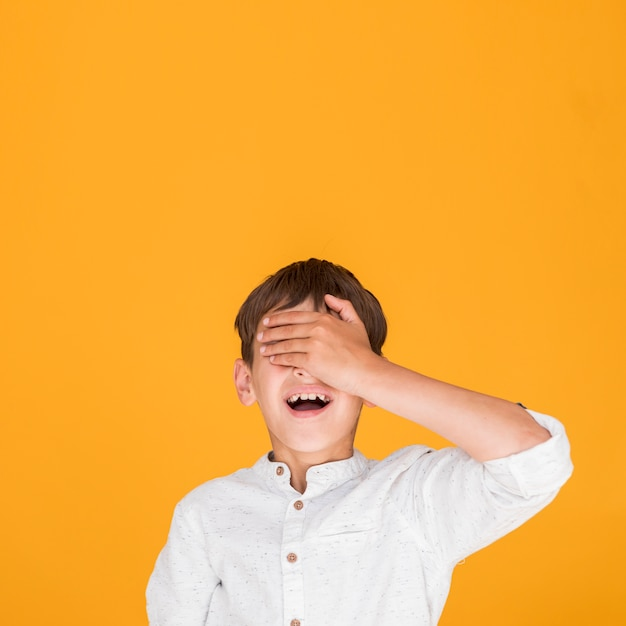 Little kid covering his eyes with copy space Free Photo