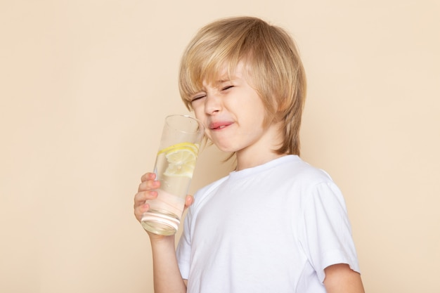 Little kid cute adorable drinking lemon juice in white t-shirt on pink wall Free Photo