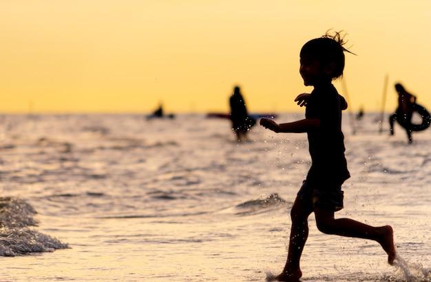 Little kid running on a sand beach silhouette Premium Photo