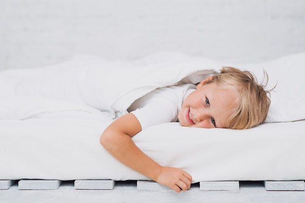 Little kid staying in bed while looking at the camera Free Photo