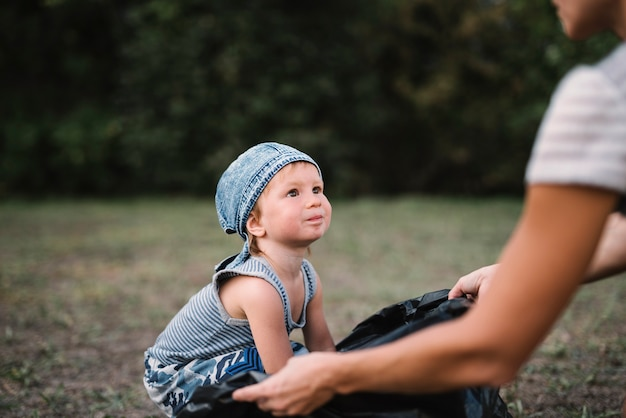 Little kid staying with parent outside Free Photo