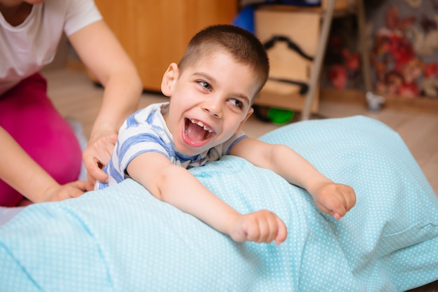 Little kid with cerebral palsy has musculoskeletal therapy by doing exercises Premium Photo