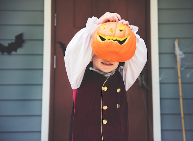 Little kid with halloween pumpkin Premium Photo