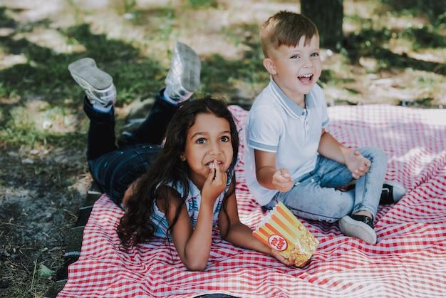 Little kids have pop corn in park family picnic Premium Photo
