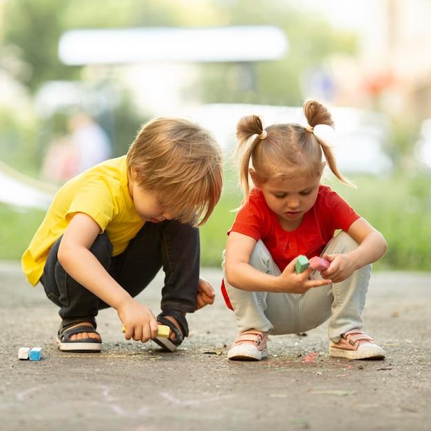 Маленькие дети в парке рисования мелом Premium Фотографии