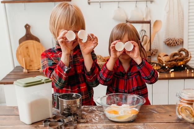 Bambini piccoli che producono i biscotti di natale Foto Gratuite
