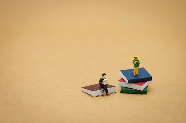 Little kids miniature people standing on books using as background education Premium Photo