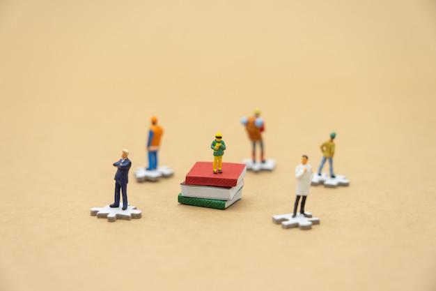 Little kids miniature people standing on books Premium Photo