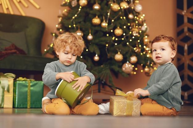 Little kids near christmas tree in a gray sweater Free Photo