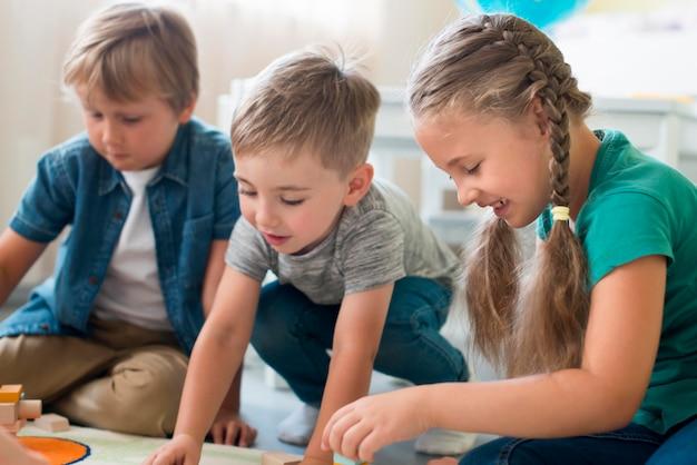 幼稚園で一緒に遊ぶ小さな子供たち 無料写真