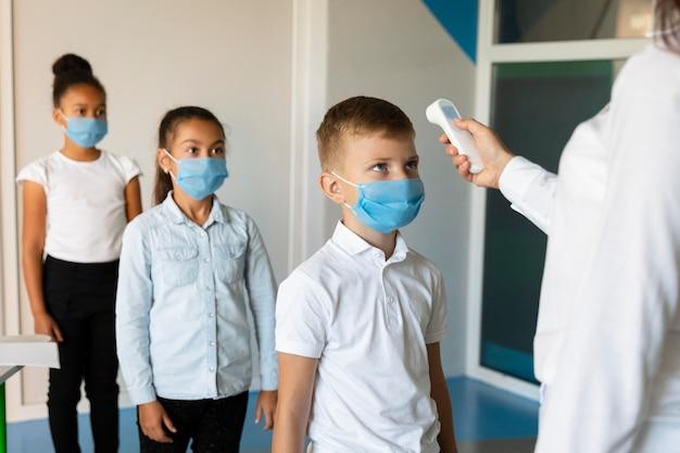 先生が体温を測るのを待っている小さな子供たち 無料写真