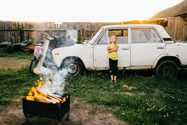 Little lovely cutie girl with importrant face standing at old vintage broken car in countryside court. autumn weekend. sunset sunlight. mess outdoor.bbq with burning firewood. rural kids lifestyle Premium Photo