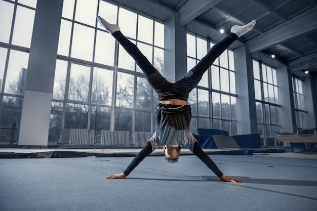 유연하고 활동적인 체육관에서 작은 남자 체조 훈련. 백인 맞는 어린 소년, 운동복에 운동 선수가 힘, 균형을 위해 연습합니다. 움직임, 행동, 움직임, 역동적 인 개념. 무료 사진