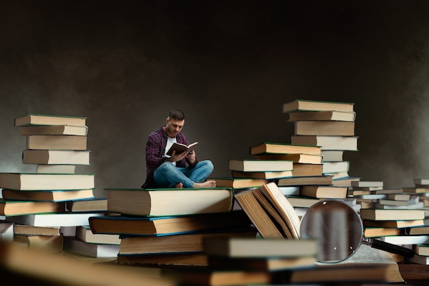 Little man reading among large books and textbooks, scale effect. gaining knowledge and education concept. student studying the subject before the exam Premium Photo
