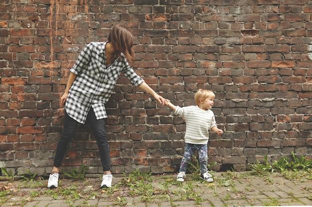 おじいさんを引っ張って先に進む小さな甥。レンガの壁の近くの場所に立っているチェックのシャツ、黒いズボンの少女。ジーンズと裸のセーターを着た小さな子供は、彼女の叔母に彼についていくことを望んでいます。 無料写真