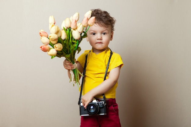 Little photographer, a child with a camera in their hands and flowers. bouquet of tulips for mother's day. Premium Photo