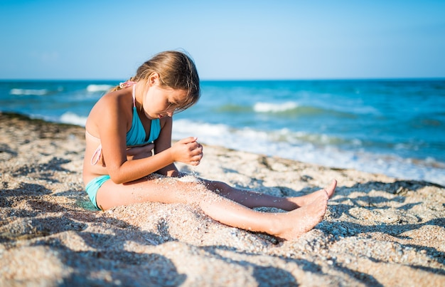 긍정적 인 소녀는 해변에 앉아서 휴가 기간 동안 화창한 여름 날에 바다 파도를 즐깁니다. 프리미엄 사진