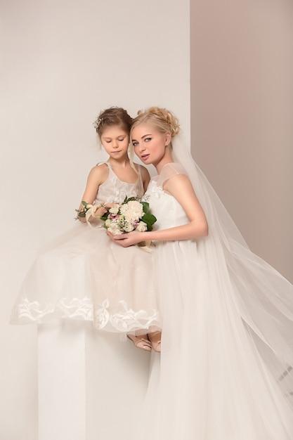 ウェディングドレスに身を包んだ花と小さなかわいい女の子 無料写真