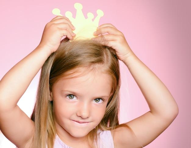 金の王冠を持つ小さな女王子少女。 Premium写真