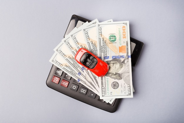 Little red car over calculator and pile of money dollars. car loan ...