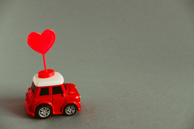 Little red toy car carries a red heart Premium Photo