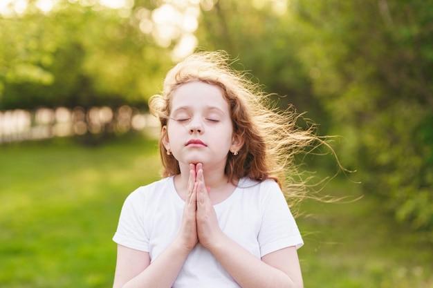 Little redhead girl  raises her hands with praying Premium Photo