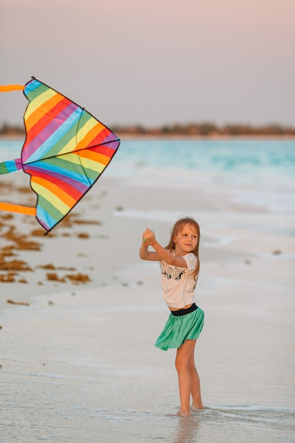 Little running girl with flying kite on tropical beach. kid play on ocean shore. Premium Photo