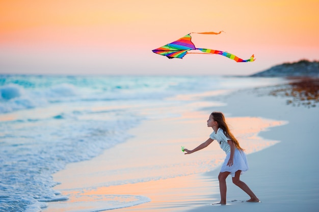Little running girl with flying kite on tropical beach at sunset. kids play on ocean shore. child with beach toys. Premium Photo