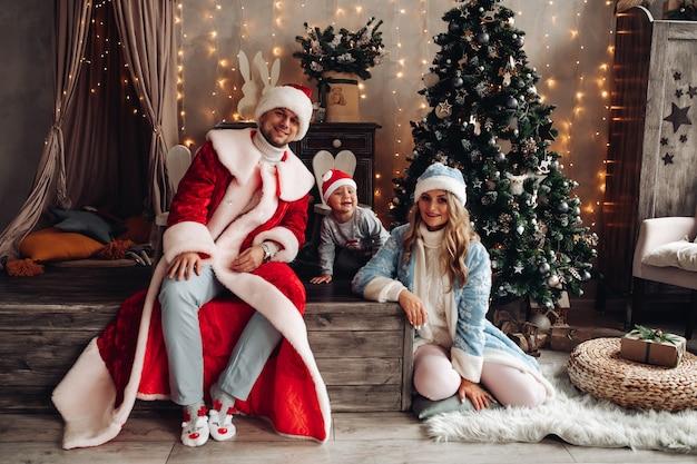 Маленький санта, дед мороз и снегурочка, улыбаясь в рождественском интерьере с украшенной елкой. Бесплатные Фотографии
