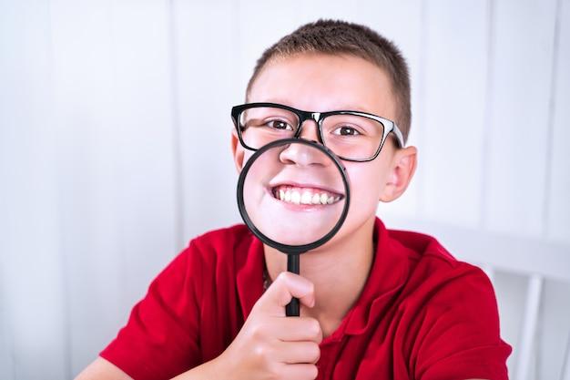 小さな男子生徒は虫眼鏡を通してポジティブな感情とネガティブな感情を表現します。学校へ戻る。感情を表現する方法を教育します。 Premium写真
