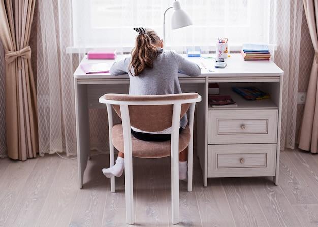 Little school girl doing homework Premium Photo