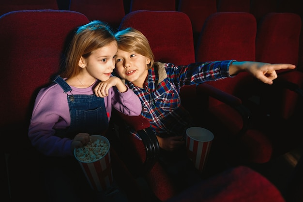 Little sister and brother watching a film at movie theater Free Photo
