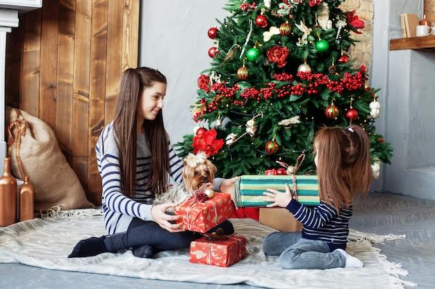 Маленькие сестры открывают подарки. Premium Фотографии