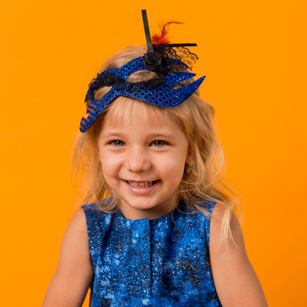 Little smiley girl in costume with mask Free Photo