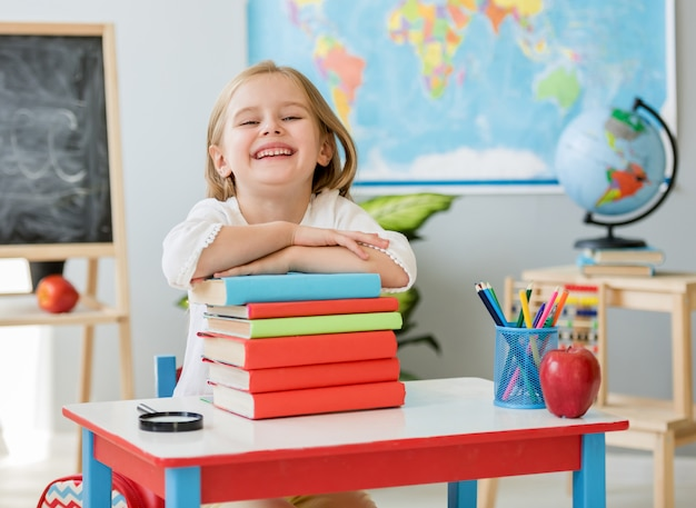 Little smiling blond girl sitting at the white desk and holding hands on the books in the spacious school class Premium Photo