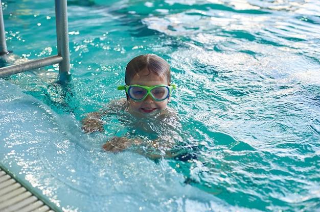 Маленький улыбающийся мальчик плавает в бассейне. крупный план. Premium Фотографии