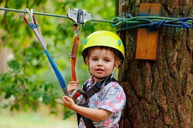 Little smiling child boy in adventure park in safety equipment in summer day Premium Photo