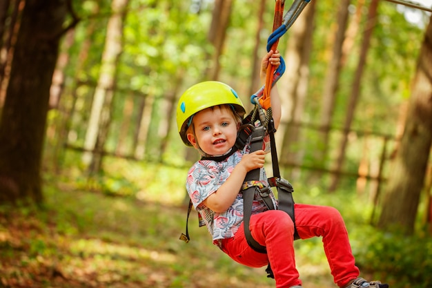 Little smiling child boy in adventure park in safety equipment in summer day. Premium Photo