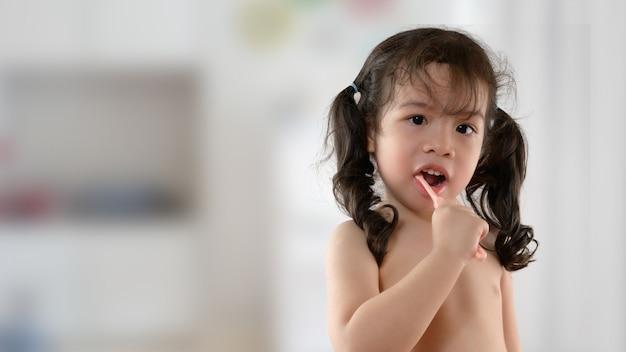 Little smiling curly asian girl brushing teeth portrait. child girl smiling while brushing her teeth. health care, dental hygiene Premium Photo