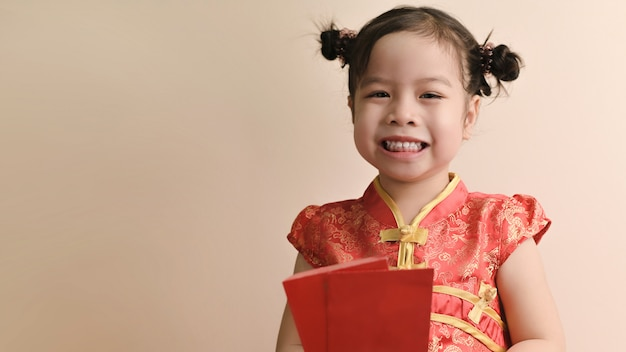 Little smiling curly asian girl hold red envelopes and smile Premium Photo